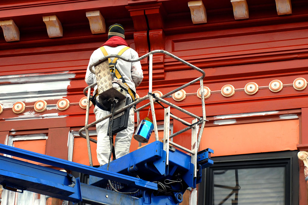 painter-painting-building-standing-in-platform-lift