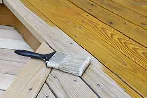 paintbrush-lying-on-partially-stained-timber-decking