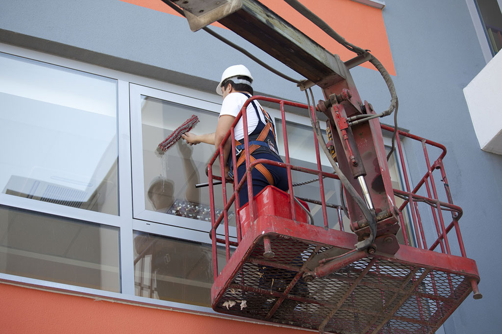 worker-cleaning-high-windows-in-commercial-building-from-cherry-picker