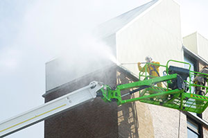 worker-on-cherry-picker-power-washing-high-industrial-building