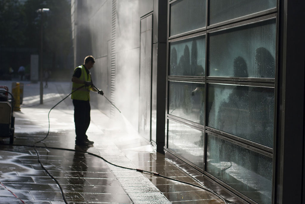worker-power-washing-exterior-of-commercial-building-from-the-street